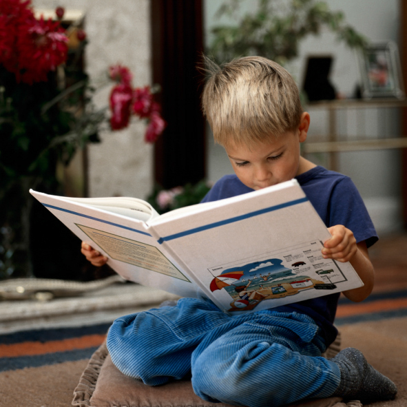 Kneeling boy reading book at home
